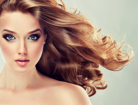 Young woman is dressed up in a  vivid make up, is touching own face and hair. Attractive woman with face full of emotions. Voluminous, shiny and wavy hair,black eyelashes and  gilded eyelids.