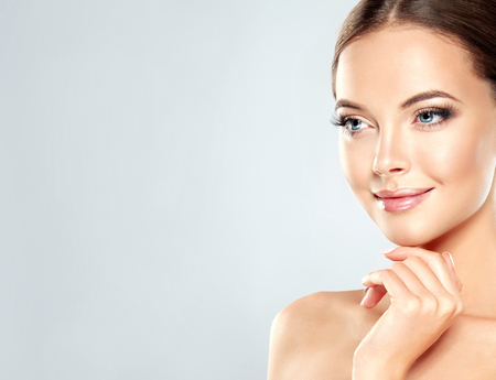 Gorgeous, young, brown haired woman with clean fresh skin touchs the face. Facial treatment, cosmetology, beauty technologies and spa.