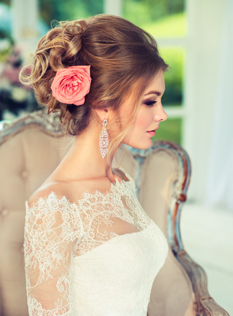 Pale rose rose on the voluminous wedding hair dress. Portrait in profile. Young, attractive bride in gorgeous and posh wedding gown. Perfect wedding hairstyle for long hair, luxurious bridal jewelry and outfit. Stock Photo