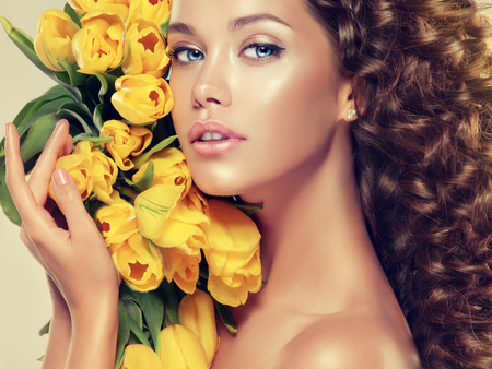 Young brown haired model with dense, curly,voluminous hair is holding bouquet of yellow tulips near the face. Simbol of spring, summer and freshness. Banco de Imagens