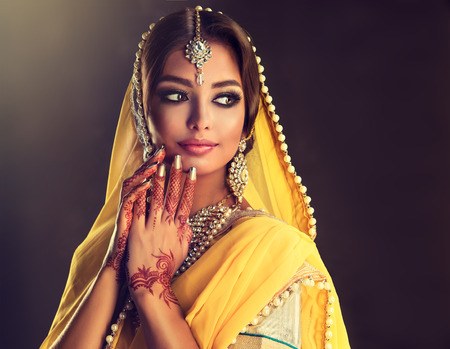 Portrait of beautiful indian girl dressed in a traditional national suit-sari,  mehndi henna tattoo is  painted on her hands and traditional kundan style jewelry set. Black haired indian young woman put on  in a posh outfit lehenga choli. Imagens