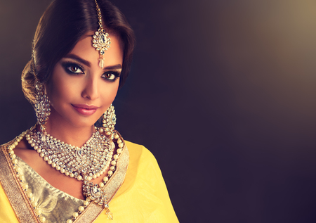 Portrait of beautiful indian girl dressed in a traditional national suit-sari,  mehndi henna tattoo is  painted on her hands and traditional kundan style jewelry set. Black haired indian young woman put on  in a posh outfit lehenga choli. 版權商用圖片