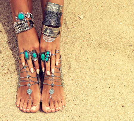 Womans hands and legs covered by bracelets and rings in a Boho style.Woman is sitting in relaxed position on tropical sandy beach. Body parts.