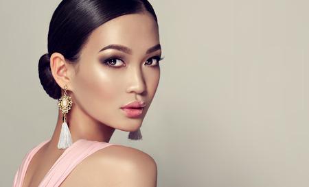 Joven, magnífico modelo de moda asiático puesto en un estilo de ojos ahumados componen, el pelo negro esparcido en una viga. vestidos con pendientes de borla y vestido rosa. Belleza oriental.