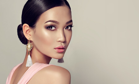Young, gorgeous asian fashion-model put on in a smoky eyes style make up, black hair gattered in a beam. dressed in tassel earrings and  pink gown. Oriental beauty. Stok Fotoğraf - 84791654