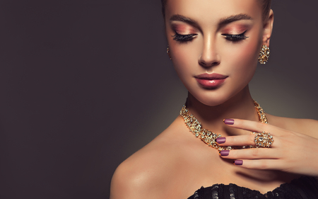 Beauty portrait of young gorgeous woman is dressed in a jewelry set of necklace, ring and earings. Pretty  blue eyed model is demonstrating an attractive make up and manicure.