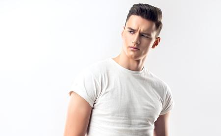 Mode portret van een knappe, jonge en serieuze man met trendy kapsel, gekleed in een wit overhemd.