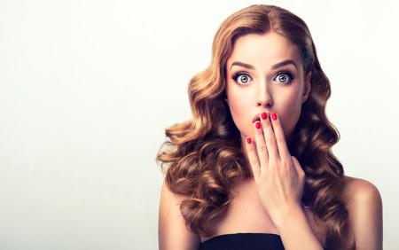 Uiting van verbazing en verbazing op het gezicht van een perfect uitziende, jonge, mooie vrouw. Make-up in pin-upstijl en rode manicure.