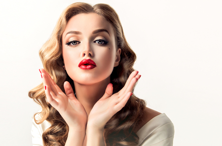 Beautiful woman  looks like a star of a retro movies . Vintage pin-up   girl  is sending air  kiss . Model with  curly hair and  bright makeup.