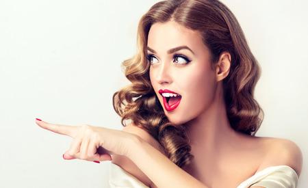 Verraste vrouw geeft aan onzichtbaar product. Mooi meisje met krullend haar naar de zijkant. Heldere gelaatsuitdrukking van opwinding, bewondering.