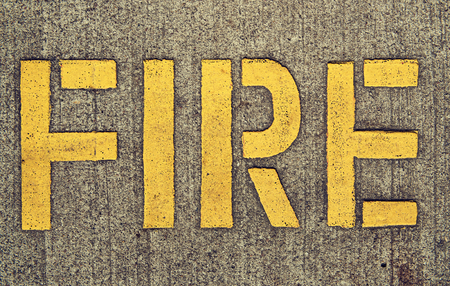 Yellow inscription Fire on the surface of asphalt road. Sign of attention and alertness.Background texture.