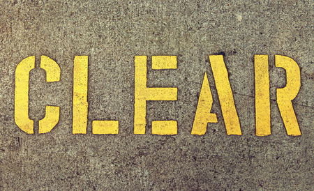 Yellow inscription clear on the surface of asphalt road. Sign of attention and alertness.Background texture.