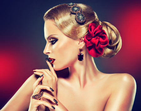 Retro style hairstyle,smokey eyeshadow and bright red lipstick on the face of young model. Elegant gesture of hands decorated by jewelry rings and black manicure. Stockfoto