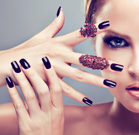 Close-up portrait of  young beautiful model is showing stylish make up in black color, and black manicure on the fingers covered by jewelry rings.