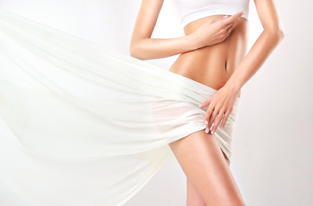 Part of attractive woman body, hips and slender toned belly, covered by tender, silk textile. Graceful female figure, as a symbol of health and harmony. Stock Photo
