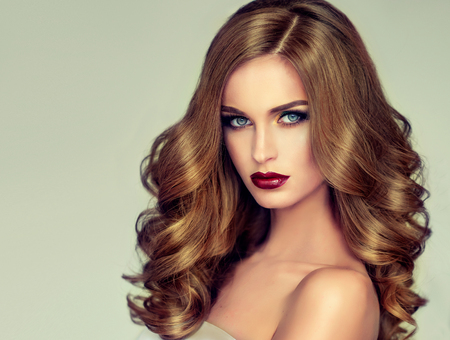 Young, brown haired woman  with voluminous hair. Beautiful model with long, dense and curly hairstyle and vivid make-up. Banque d'images