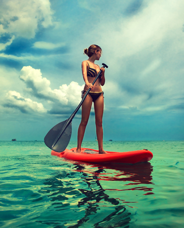 A jovem mulher esbelta vestida com um maiô de biquíni está navegando no conselho com uma paddle. Exemplo de entretenimento no mar, estilo de vida ativo e esporte aquático.