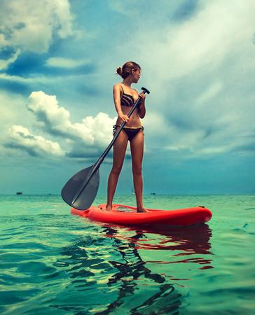 Giovane donna snella vestita in un costume da bagno di bikini sta navigando sulla tavola che governa la pagaia. Esempio di intrattenimento sul mare, stile di vita attivo e sport acquatico.