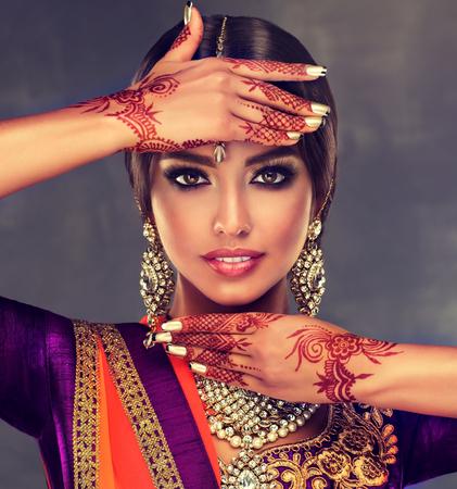 Porträt des schönen indischen Mädchens, das in einer traditionellen nationalen Klage und in einer mehndi Tätowierung gekleidet wird, wird auf ihren Händen gemalt.