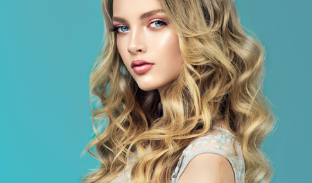 Young, blond haired woman  with voluminous hair. Beautiful model with long, dense and curly hairstyle and vivid make-up. Tender and soft look, beauty of youth and innocence. Stock Photo