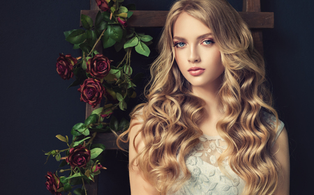 Young, blonde haired beautiful model with long, wavy,well groomed hair. Stylish, loose hairstyle with freely lying curls. Banco de Imagens