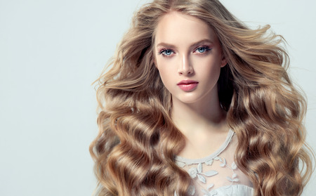 Jeune femme aux cheveux blonds aux cheveux volumineux. Beau modèle avec une coiffure élégante et ample avec des boucles librement allongées et un maquillage vif.