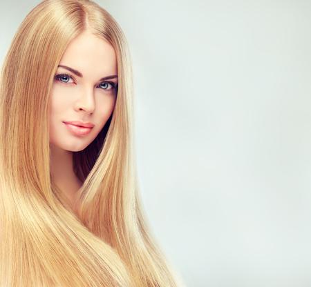 Jonge, blonde vrouw met lang, recht, gezond en glanzend haar. Mooi model met lange, rechte, kapsel, delicate make-up en lichtrose lippenstift op de lippen.