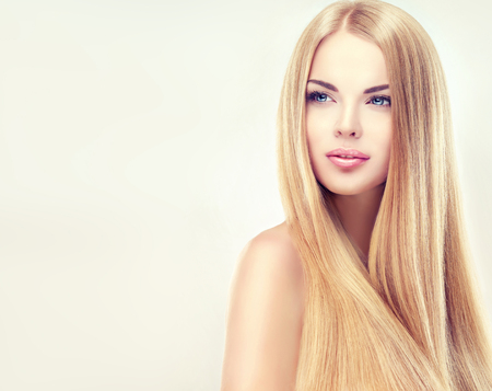 Young, blonde haired woman  with long, straight, healthy and shiny hair. Beautiful model with long, straight,  hairstyle, delicate make-up and  pale rose lipstick on the lips.
