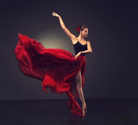 Balerina. Młoda tancerka baletowa z wdzięku kobiety, ubrana w strój zawodowy, buty i czerwona bez rękawów spódnica wykazuje umiejętności tańca. Piękno klasycznego baletu.