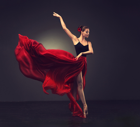 Ballerina. Young graceful woman ballet dancer, dressed in professional outfit, shoes and red weightless skirt is demonstrating dancing skill. Beauty of classic ballet. Stock Photo - 87764957