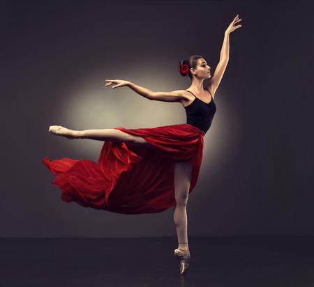 Ballerina. Der junge würdevolle Frauenballetttänzer, gekleidet in der Berufsausstattung, in den Schuhen und im roten schwerelosen Rock demonstriert Tanzenfähigkeit. Schönheit des klassischen Balletts. Standard-Bild