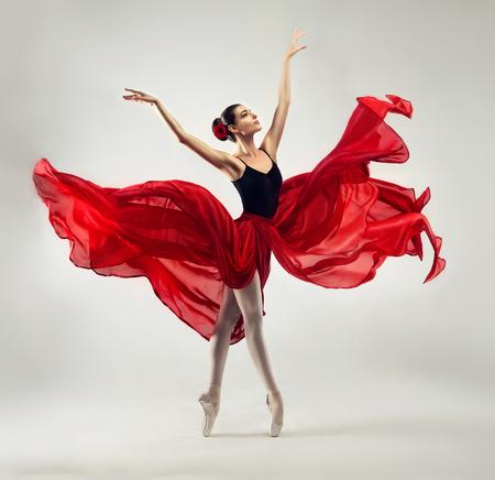 Ballerina. Der junge würdevolle Frauenballetttänzer, gekleidet in der Berufsausstattung, in den Schuhen und im roten schwerelosen Rock demonstriert Tanzenfähigkeit. Schönheit des klassischen Balletts.