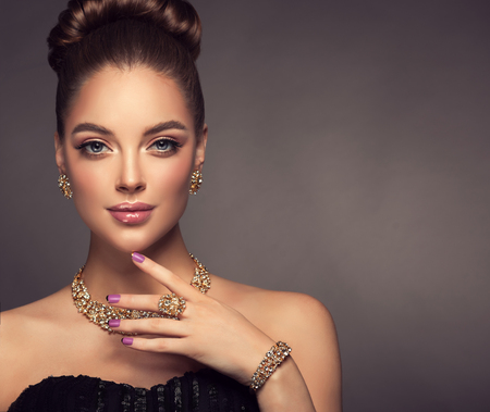 Magnificent lady in a perfect make up is shows jewelry set.