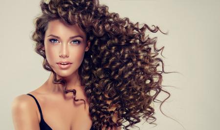 Joven, bella modelo de cabello castaño con cabello largo, ondulado y bien arreglado. Rizos tensos y primaverales en el cabello.