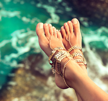 Tanned, slender, well groomed womans feet dressed in a gilded leg bracelets in Boho style above green water of tropical sea. Body parts. Stok Fotoğraf