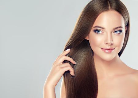 Joven, hermosa modelo de cabello castaño con cabello largo, liso y bien peinado toca su propio cabello con ternura.