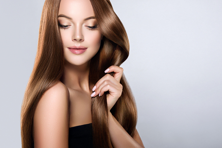 Young, brown haired woman  with voluminous hair.Beautiful model with long, dense, straight hairstyle and vivid makeup, is touching own hair with tenderness. Symbol of attentiveness to hair and good care of it.