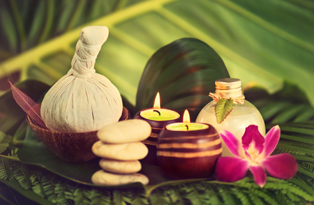Spa still life with herbal ball, lightened candles, orchid flower, coconut oil for massage treatments and herbal soap, standed on green tropical leaves.