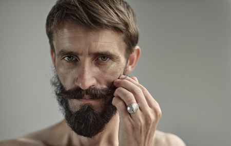 Bearded middle-aged handsome man in touching own moustache by finger tips. Wrinkled face and hipster style beard and moustache.