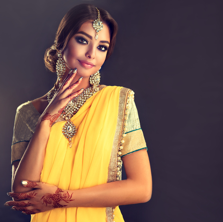 Portrait of beautiful indian girl dressed in a traditional national suit,  mehndi henna tattoo is  painted on her hands and traditional kundan style jewelry set. Black haired indian young woman dressed  in a posh yellow sari costume.