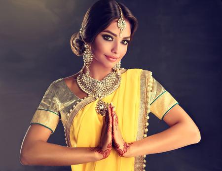 Retrato de menina indiana bonita vestida com um terno nacional tradicional, a tatuagem mehndi henna é pintada em suas mãos e o conjunto tradicional de jóias de estilo kundan está mostrando um gesto de saudação - namaste. Foto de archivo - 91087771