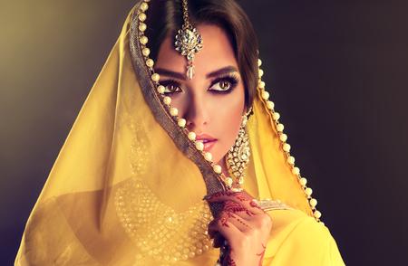 若いインド人女性の肖像画に近い白い真珠と黄色の布で顔の部分を覆っています。明るいメイクアップ、長いまつげと入札の注意をそらす。 写真素材