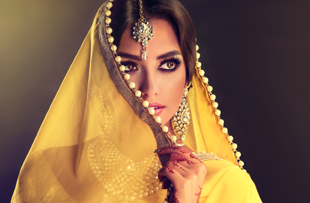 Close up portrait of young indian woman is covering part of the face by yellow cloth with white pearls. Bright make up, long eyelashes and tender look aside.