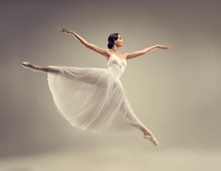 Ballerina. Der junge würdevolle Frau Balletttänzer, gekleidet im klassischen, weißen Chopin-Ballettröckchen und in den Berufsballettschuhen demonstriert Tanzenfähigkeit. Schönheit des klassischen Balletts.