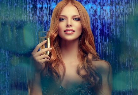 Young, red haired gorgeous woman is holding a glass of champagne wine. Hospitality  and readiness to celebrate in a her tender look. Stock Photo