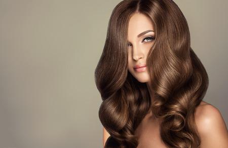 젊은, 갈색 머리 여자와 방한 머리. 길고, 조밀하고 곱슬 머리 스타일과 생생한 메이크업의 아름다운 모델. 완벽한 헤어 컬 및 섹시한 look.Incredibly 밀도,