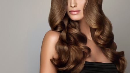 Jeune femme aux cheveux bruns aux cheveux volumineux. Beau modèle avec une coiffure longue, dense et frisée et un maquillage éclatant. Cheveux parfaits. Cheveux incroyablement denses, ondulés et brillants.