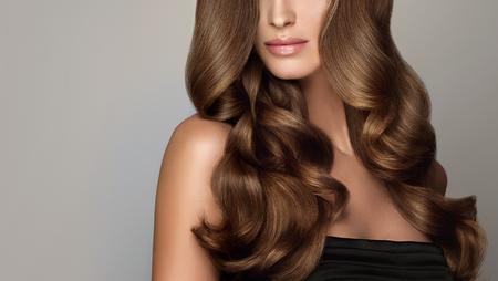 Junge, braunhaarige Frau mit voluminösen Haaren. Schönes Modell mit langer, dichter und lockiger Frisur und lebhaftem Make-up. Perfektes Haar. Unglaublich dichtes, welliges und glänzendes Haar.