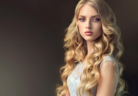 Jong, blond haired mooi model met lang, golvend, goed verzorgd haar. Stijlvol, los kapsel met vrijliggende krullen.