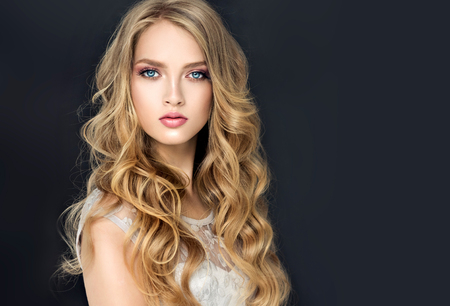 Young, blonde haired beautiful model with long, wavy,well groomed hair. Stylish, loose hairstyle with freely lying curls. 写真素材